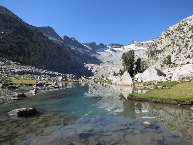 This lovely snow-fed tarn sits on a bench below Donahue Pass.