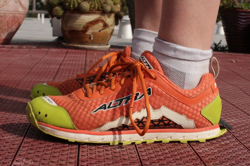 "Altra Lone Peak 1.5s, side view. In the super neutral ""traffic orange"" color scheme."