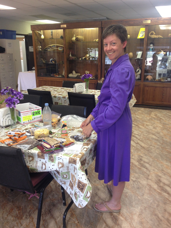 Alice sorting her first resupply box at the Warner Springs Community Center in a purple loaner dress.