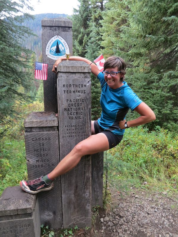 Alice/Penguin climbing on Monument 78 at the northern terminus of the PCT
